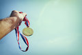 Man hand raised holding gold medal against sky award and victory concept selective focus retro style image Stock Photos