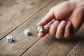 Man hand throwing white dice on wooden table. Gambling devices. Game of chance concept. Royalty Free Stock Photo