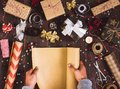 Man hand unfolding roll of wrapping kraft paper for packing christmas gift box Royalty Free Stock Photo