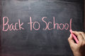 Man hand writing back to school on blackboard. Royalty Free Stock Photo