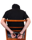 Man in handcuffs on the chair rear view and closeup Royalty Free Stock Image