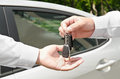 Man handing another person automobile keys new car outdoors Royalty Free Stock Photos