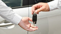 Man handing another person automobile keys new car outdoors Stock Images
