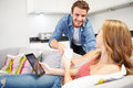 Man handing woman drink as she uses digital tablet at home lying on sofa Royalty Free Stock Photography