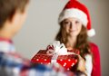 Man handing woman gift red wrapped to a beautiful Royalty Free Stock Photography