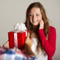 Man handing woman gift red wrapped to a beautiful Royalty Free Stock Images