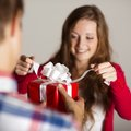 Man handing woman gift red wrapped to a beautiful Royalty Free Stock Image