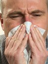 Man with handkerchief blows his nose in a Royalty Free Stock Photos