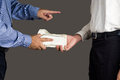 Man handling an envelope full of money to another person with finger pointing while his Royalty Free Stock Photos