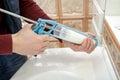 Man hands applying silicone sealant.