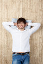 Man with hands behind head relaxing on wooden wall handsome young Stock Image