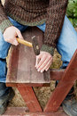Man hands drive nail with a hammer in wooden bench carpentry Royalty Free Stock Photos