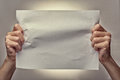 Man hands holding a crumpled blank piece of paper Royalty Free Stock Photo