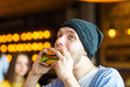 Man in hands holds a burger. Man eating a burger at the cafe Royalty Free Stock Photo