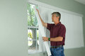 Man hanging vertical blinds home repair maintenance