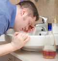Man with hangover washing up Royalty Free Stock Photography