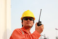 Man in hard hat using walkie talkie for comunication Royalty Free Stock Photo
