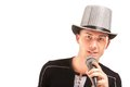 Man in the hat sings expressively into microphone.