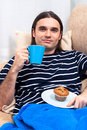Man having breakfast on sofa Royalty Free Stock Photos