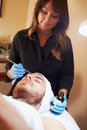 Man having dermo abrasion cosmetic treatment at spa by beautician Stock Photography