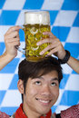 Man having Oktoberfest beer stein on head Royalty Free Stock Photography