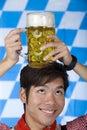 Man having Oktoberfest beer stein on head Royalty Free Stock Photography