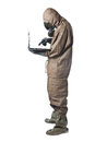 Man in hazard suit using a laptop wearing an nbc suite nuclear biological chemical Royalty Free Stock Photos