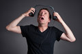 Man with a headphone middle age holding away the from his ears while sufferingr Stock Photo