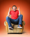 Man in headphones has jumped up in an armchair Stock Photo