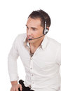Man with a headset listening to a call attractive wearing sitting in shirtsleeves high angle studio portrait isolated on white Royalty Free Stock Images
