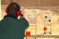 Man with hearing protection shooting gun at pistol range Royalty Free Stock Photo