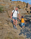 Man helping his son to hike on a rough area rear view of men stony of the mountain in summer Royalty Free Stock Image