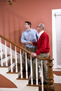 Man helping senior father climb stairs at home Royalty Free Stock Photo