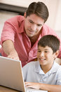 Man helping young boy in kitchen with laptop Royalty Free Stock Photography