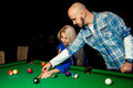 Man helps a girl to play pool on the billiard table Royalty Free Stock Photo