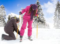 Man helps her girlfriend to put her skis young men on winter background Royalty Free Stock Image