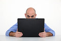 Man hiding behind laptop Royalty Free Stock Image