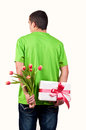 Man hiding flowers and gift box behind his back tulips Stock Photo