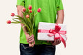 Man hiding flowers and gift box behind his back tulips Stock Image