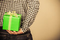 Man hiding gift box behind back. Holiday surprise. Royalty Free Stock Photo