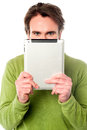 Man hiding his face with tablet device young guy e book reader Stock Images