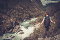 Man hiker with backpack standing on the edge of the cliff with epic wild mountain river view.