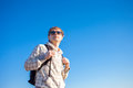 Man hiker holding backpack on a sunny day against a blue sky happy Royalty Free Stock Photo