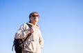 Man hiker holding backpack on a sunny day against a blue sky happy Stock Photography