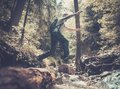 Man hiker jumping across stream in mountain forest Royalty Free Stock Image