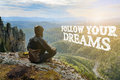 Man hiker sitting on top of mountain and contemplates beautiful view to the valley. Follow your Dreams lettering. Royalty Free Stock Photo