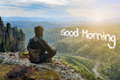 Man hiker sitting on top of mountain meeting sunrise, Good Morning lettering in form of clouds.