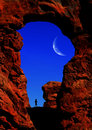 Man hiking in arches national park silhouette of under an arch Royalty Free Stock Photo
