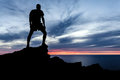 Man hiking silhouette in mountains ocean and sunset male hiker with backpack on top of mountain looking at beautiful night Stock Photos