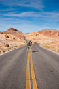 A man and his camera in middle of road looking for perfect shot in valley of fire usa Royalty Free Stock Photo
